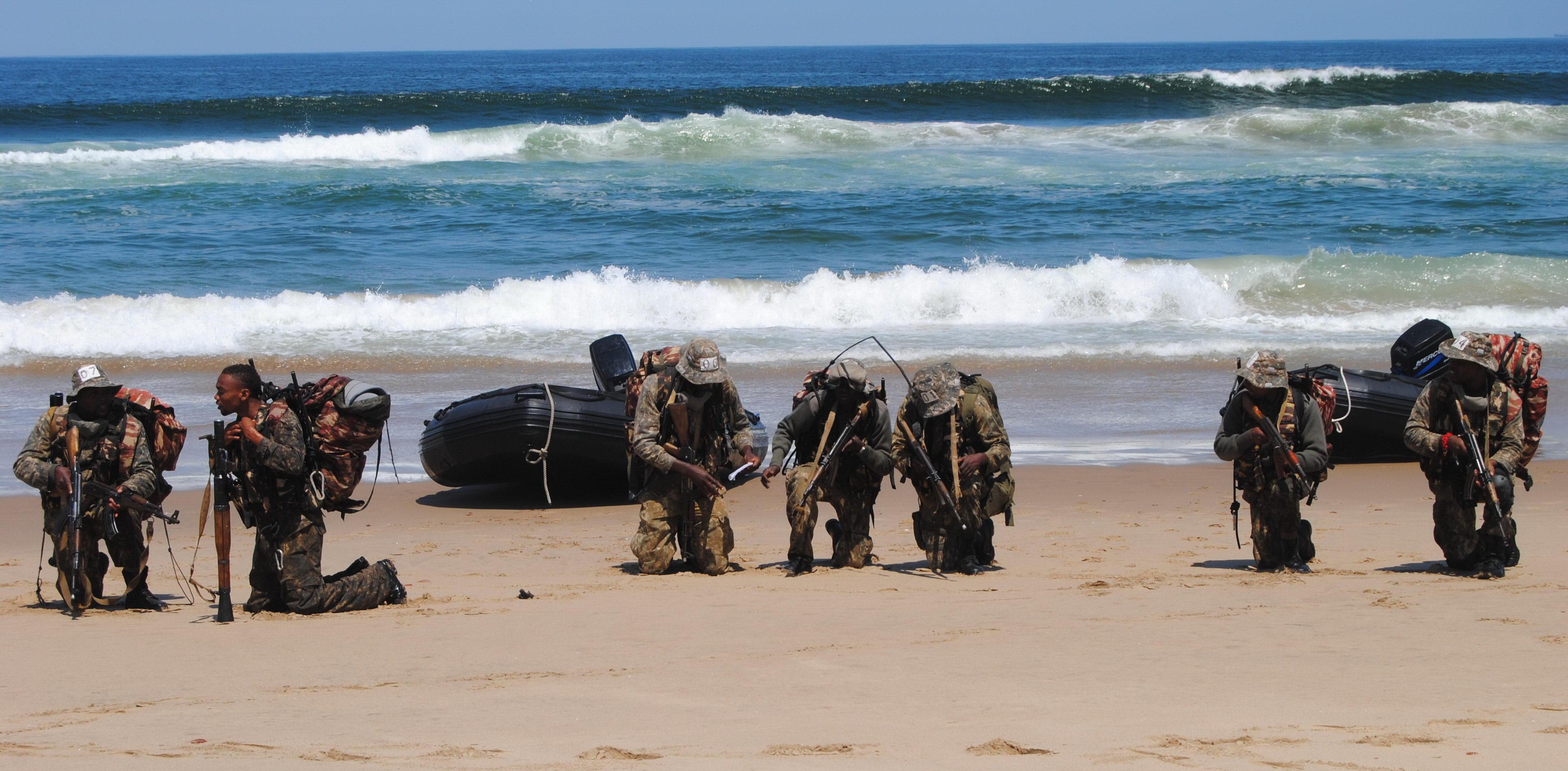 Já na praia, os alunos do Ades-Bas-OpEsp, armados com fuzis AK calibre 7,62x39mm e lançadores de granadas-foguete RPG-7, preparam-se para o deslocamento de 14 km até a fictícia base de piratas. (Imagem: Comando Geral do Corpo de Fuzileiros Navais)