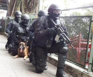 """Aguardando os possíveis resultados de uma negociação em andamento com o """"terrorista"""", equipe mista do BOPE/BAC prepara-se para entrar em ação direta. (Imagem: Ronaldo Olive)"""