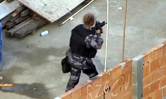 Policial militar do Batalhão de Polícia de Choque (BPChq) progredindo numa comunidade carioca armado com fuzil ArmaLite AR-10A4. A mira holográfica EOTech 552 está visível na foto. (Imagem: Oyoy Kanamox)