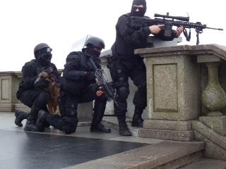 Contando com o apoio de um atirador de precisão e seu fuzil ArmaLite AR-10 SuperSASS (7,62x51mm), integrante do GRR armado com carabina Colt M16A2 Commando (5,56x45mm) e o condutor de cães do BAC preparam-se para entrar em ação no alto do Corcovado. (Imagem: Ronaldo Olive)